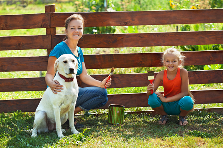 animal family: Teamwork - woman with little girl and dog painting a fence in summer time Stock Photo