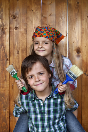 repaint: Kids ready to repaint wooden wall - holding brushes and smiling