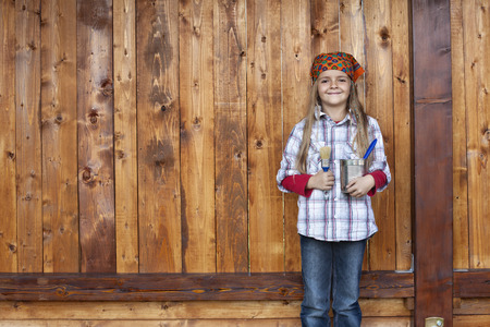 repaint: Happy little girl proud to repaint the wood shed - standing in front of wooden plank wall, large copy space