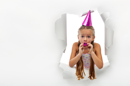 Surprise - little girl with party horn popping out from a torn paper sheet - with copy space Stock Photo