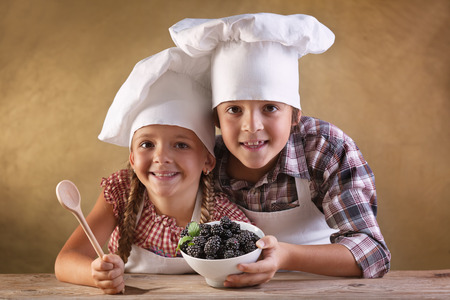 eat right: Eat right concept - kids with chef hats holding blackberries in a bowl