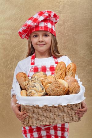 breadbasket: Little baker girl holding basket with fresh bakery products