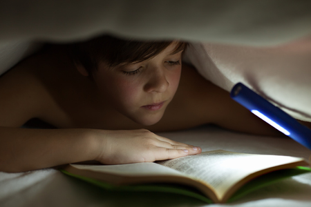 Young boy reading a book under the blanket or quilt - lighting with a flashlight Zdjęcie Seryjne - 75638522