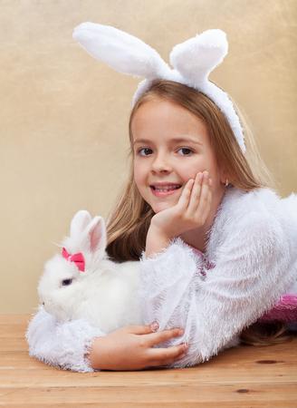 fleecy: Little girl in bunny costume holdng her white rabbit lying on the floor