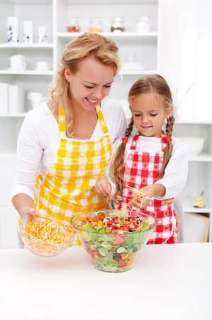 Educating kids for healthy lifestyle choices - mother and young daughter preparing vegetables salad together photo