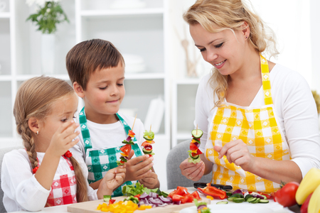 Young kids with their mother in the kitchen preparing a vegetables snack - healthy eating concept photo