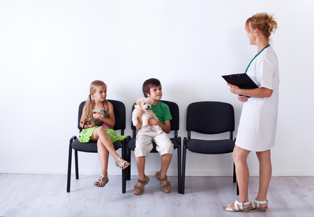 Kids taking their pets to the veterinary doctor - sitting and holding their furry friends photo