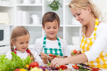 Closeup of young kids with their mother in the kitchen - preparing a healthy vegetables meal together photo