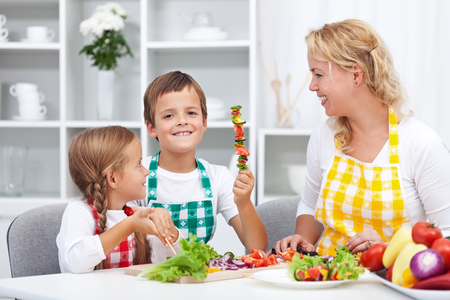 Happy young kids preparing a healthy snack with their mother - having fun in the kitchen photo