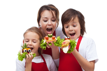 Kids and woman taking a bite of funny creatures sandwiches - isolated photo