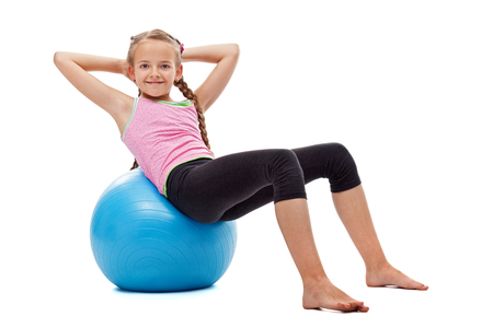 Happy young girl doing abdominal gymnastic exercises sitting on large rubber ball and smiling - isolated Stock Photo
