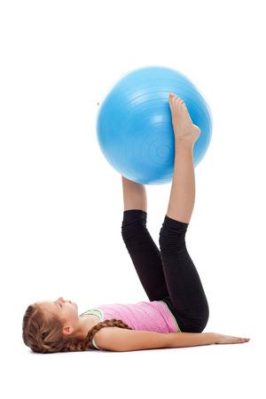 Młoda dziewczyna robi nogi i ćwiczenia gimnastyczne brzucha przy użyciu dużej gumy kula - izolowane
