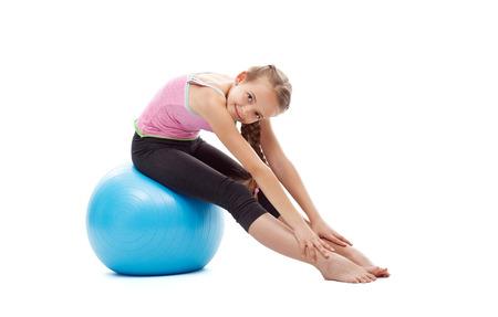 Szczęśliwa młoda dziewczyna robi rozciągania gimnastycznemu obsiadaniu na wielkiej gumowej piłce - odosobnionej