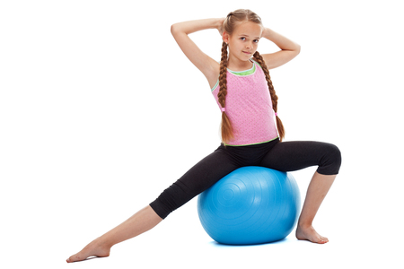 Mała dziewczynka siedzi na duże gimnastyczne gumowe piłki ćwiczenia - bilans i rozciąganie