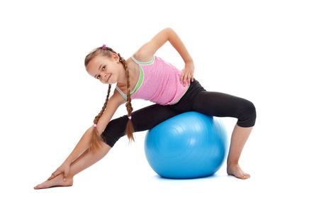 Młoda dziewczyna robi ćwiczenia rozciągające gimnastyczne siedzi na dużej gumy kuli - samodzielnie