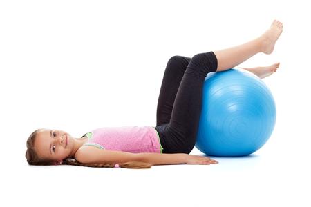 Szczęśliwa młoda dziewczyna ćwiczeń z dużą kulką gimnastyczną gumy - leżącego na podłodze uśmiecha się, izolowane