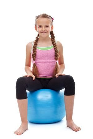 Wszystkiego najlepszego z okazji młoda dziewczyna sportowy siedzi na duży kulkowe gimnastyczne - uśmiecha się i odprężenia, samodzielnie Zdjęcie Seryjne
