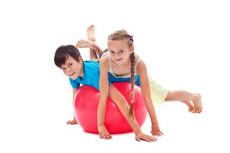 Niños que se divierten con una bola de gimnasia grande de goma - equilibrio mientras que pone en sus vientres