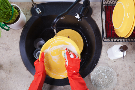 Hands in red rubber gloves washing the dishes - top view of the kitchen sink area