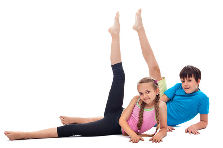 Kids doing gymnastic exercise lying on the floor and rising legs - isolated photo