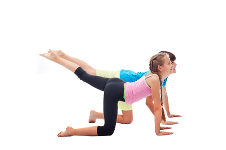 Young kids doing a gymnastic exercise on white background - stretching