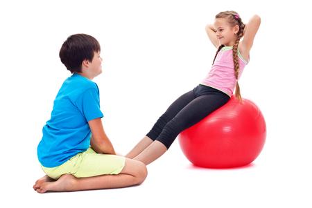 Dzieci ćwiczące razem wzmacniające mięśnie brzucha - używając dużej gumowej gali gimnastycznej Zdjęcie Seryjne