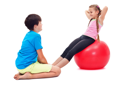 Kids exercising together strengthening abdomen muscles - using a large rubber gymnastic ball photo