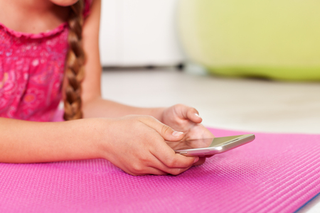 Young girl checking her phone lying on the floor at home - closeup on hands, copyspace Stock Photo