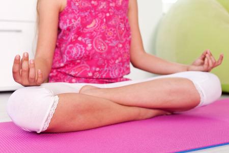 Młoda dziewczyna relaksuje w lotosowej joga pozie w domu - zbliżenie