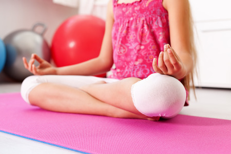 Młoda dziewczyna medytuje lub relaks w pozycji lotus jogi - siedząc na podłodze w domu lub na siłowni