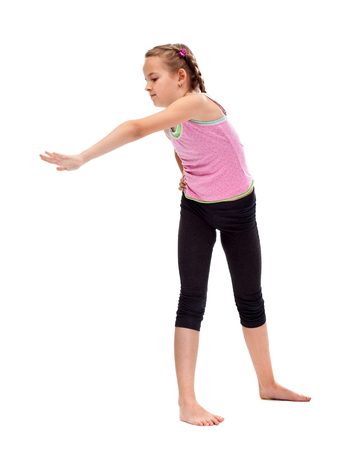 Young girl standing and doing stretching and flexibility gymnastic exercise - isolated Zdjęcie Seryjne