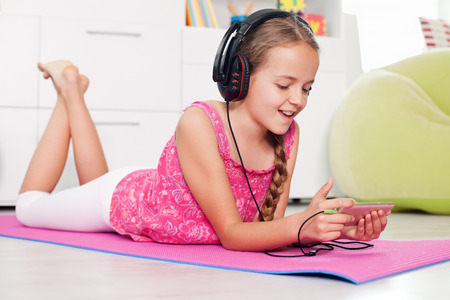 Young girl using her phone listening to music lying on the floor at home Zdjęcie Seryjne