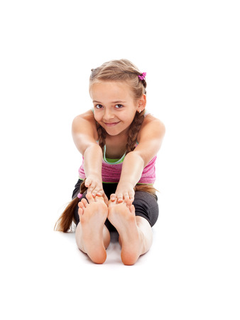 Young girl sitting on the floor and stretching - warming up for gymnastic exercise