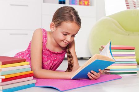 Młoda dziewczyna czytania w domu - leżącego na podłodze z książek po jej stronie