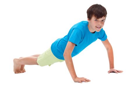 Jonge jongen doet push ups - geïsoleerd