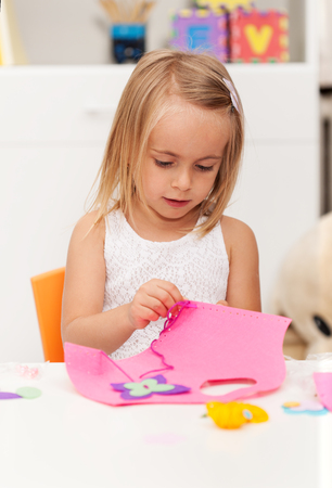 Little girl working on a crafting project - doing some needlework at home, closeup