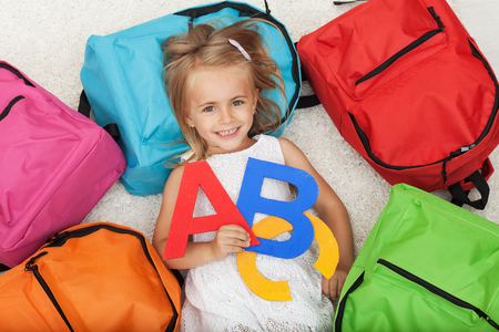 Little girl anxious to go to school - lying on the floor among colorful school bags, holding alphabet letters Zdjęcie Seryjne