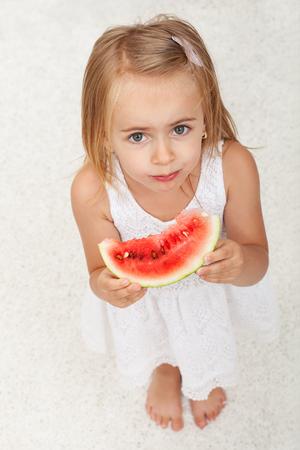 Młoda dziewczyna w białej sukni jedzenia plasterek arbuza - widok z góry, białe tło dywan Zdjęcie Seryjne