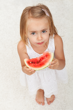 Young girl in white dress eating a slice of watermelon - top view, white carpet background Zdjęcie Seryjne