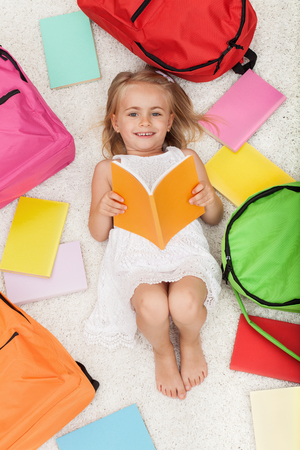 Little preschool girl lying on the floor with colorful school bags and books - smiling happily Zdjęcie Seryjne