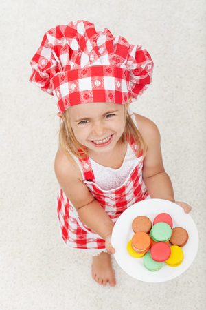 Extremely happy little chef wearing an apron and hat holding a plate of colorful cookies - looking up with a broad smile Zdjęcie Seryjne