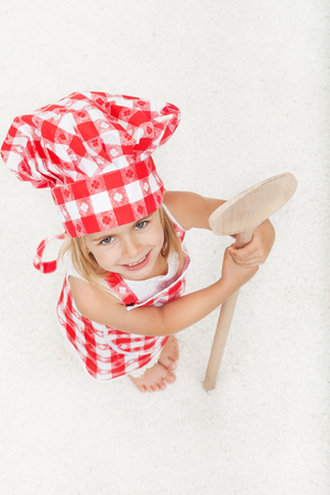 Little chef with apron and hat holding a large wooden spoon - looking up and smiling, on white background Zdjęcie Seryjne