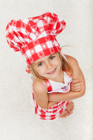 Happy little chef girl looking up and smiling with arms crossed - wearing an apron and hat