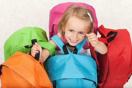 Happy preschooler girl choosing her school bag from a colorful set - smiling with joy, top view