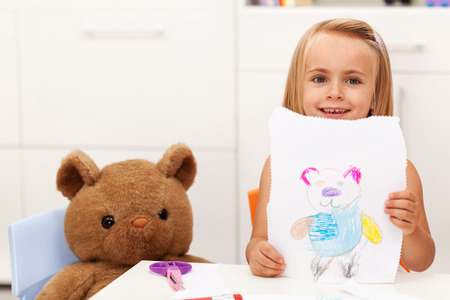Little girl presents her completed drawing - a colorful portrait of her toy bear Zdjęcie Seryjne