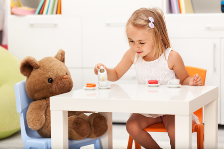 Little girl playing with her toy bear - having a tea party and some cookies, shallow depth Zdjęcie Seryjne