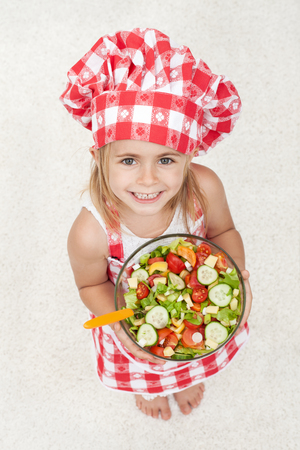 Happy little chef wearing an apron and hat holding a bowl of vegetables salad - looking up with a broad smile