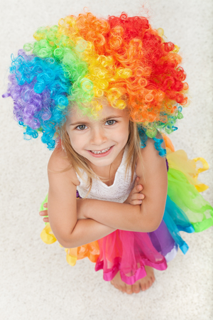 Happy little girl with colorful clown wig and a matching skirt - looking up with a large smile and hands crossed Zdjęcie Seryjne