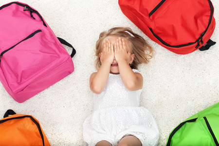 Little girl lying among colorful school bags, covering her eyes - top view