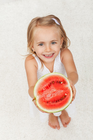 Happy little girl giving you half of a watermelon - looking up with a broad smile